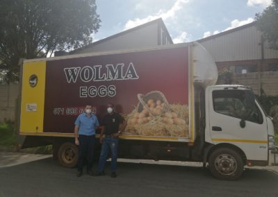Two staff members standing in front of a Wolma Delivery Van